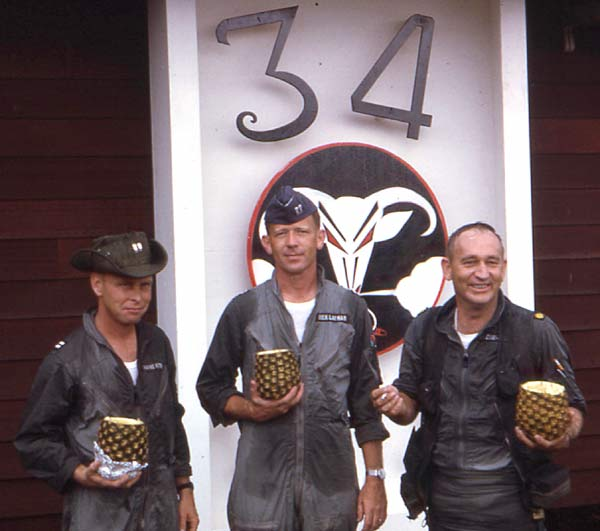 Bob Pielin was the first 34th member to complete 100 missions and these were the next 3, shown shortly after their mission in August 1966. Left to right: Wayne Hauth, Rick Layman, and Dick Fitzgerald. They flew their 100th in the same flight somewhere in Pack 1. The hollowed-out pineapples are full of rum.