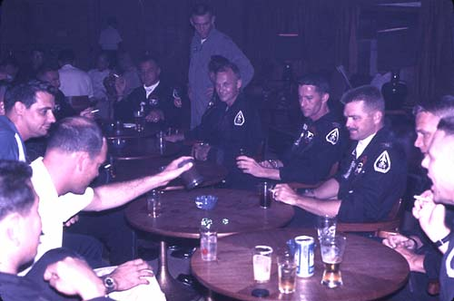 Another shot of fun at the Officer's Club. Harry Paddon at left; Don Austin rolling the dice; Hugh Davis 4th from the right; Rod Giffin 3rd from the right; Dwight E. Sullivan 2nd from right; any other ID's?