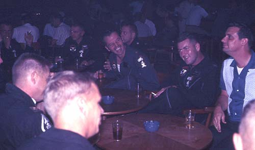 A night at the Officer's Club. Jim McClelland laughs at a joke; Bobby Martin is next to him with Harry Paddon at the far right; Dwight E. Sullivan at front left.