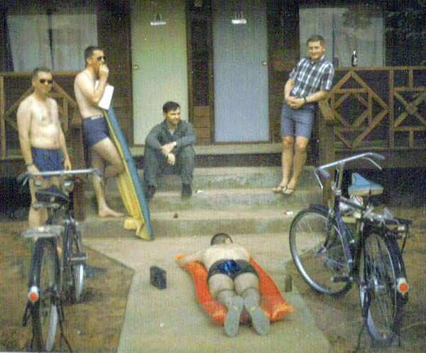 Relaxing at the hootch, circa 1965-66. Left to right: Ray Tiffin, J. R. (Rick) Layman, Stan Gunnersen, C. E. (Ed) Fox (prone on air mattress), & D. D. (Denis) O'Donoghue.