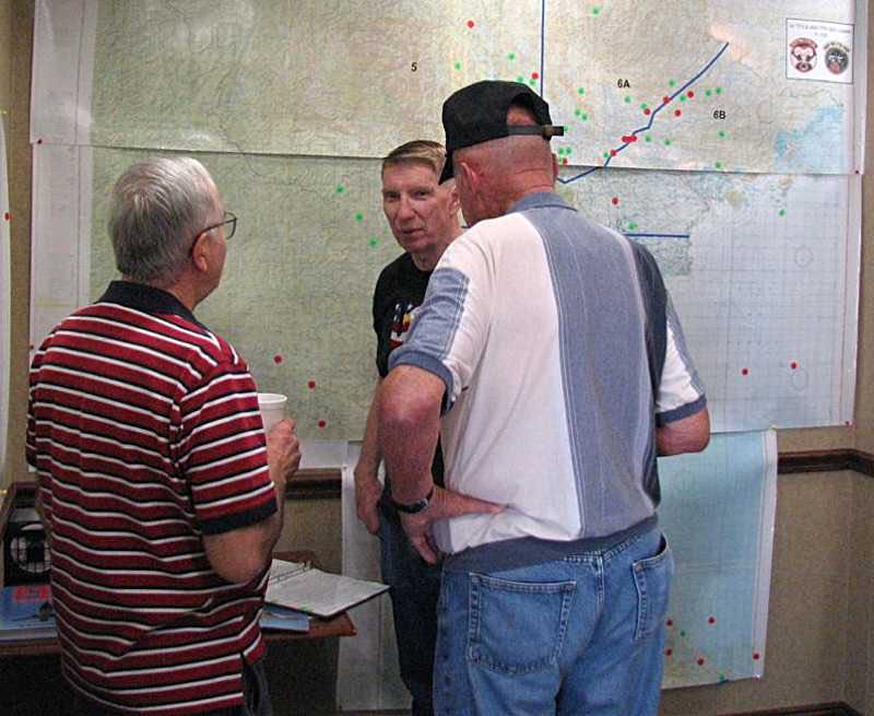 Howard Plunkett, Irv Levine & Bob Jones looking over charts.